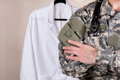 Medical military doctor with white consultation coat in backgrou. Close up partial view of medical doctor wearing military uniform and stethoscope with medical royalty free stock photo