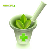 Medical mortar with pestle and a green cross. Royalty Free Stock Photo