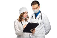 Two doctors discussing results of the analysis isolated on wh. Medical multiethnic staff having discussion in a hospital hallway. Male and female nurse wearing Stock Photos