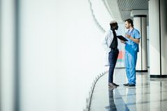 Medical multiethnic staff having discussion in a hospital hallway. Two doctors working in a medical clinic. Two hospital workers d stock photo