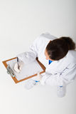 Medical nurse. An overhead view of a medical nurse writing on clipboard on white background royalty free stock photography