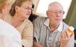 Medical Nurse Explaining Prescription Medicine to Senior Couple Stock Photo