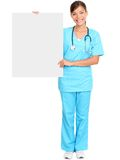Medical nurse showing blank sign. Medical doctor showing blank empty billboard sign poster. Young female doctor / nurse standing in full body isolated over white stock photography