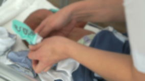 Medical nurse swaddles newborn baby on baby cot stock video footage