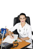 Medical office. Doctor write a medical prescription and give pills in her office,other photos with this model in royalty free stock photos