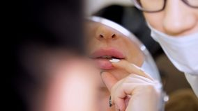Medical office, beautiful woman looking in the mirror, doctor probes the patient`s lips after injections of hyaluronic