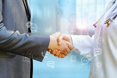 Medical officer and shaking hands with businessman. On blurred background Royalty Free Stock Image