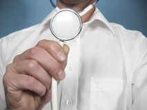 Medical Person Holds a Stethoscope. Closeup of a medical person holding the diaphragm end of an acoustical stethoscope Stock Photo