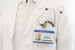 Midsection of senior doctor with identity card and stethoscope at hospital royalty free stock images