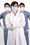 Medical Personnel. Three young medical personnel in doctors coat and scrubs Stock Photo