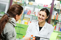 Medical pharmacy drug purchase. Pharmacist suggesting medical drug to buyer in pharmacy drugstore Stock Photo