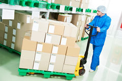 Medical pharmacy factory warehouse. Medical warehouse worker man loading boxes with medcine drugs by hand forklift at pharmacy factory stock photo
