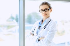 Medical physician doctor woman over blue clinic background. Royalty Free Stock Images