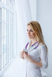 Medical physician doctor woman over blue clinic background. Royalty Free Stock Photos
