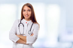 Medical physician doctor woman over blue clinic background. Royalty Free Stock Photography