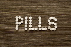 Medical pill on wooden table. Close up photo.  Royalty Free Stock Photo