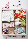 Medical pills and ampules in wooden box Stock Images