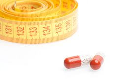 Medical pills for dieting in front of measuring tape Stock Images