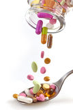Medical pills falling in spoon Royalty Free Stock Photography
