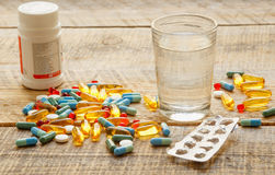 Medical pills and pack tablet with water on wodden table Royalty Free Stock Images
