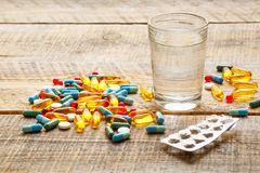 Medical pills and pack tablet with water on wodden table Royalty Free Stock Image