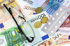 Medical pills, tablets and glasses in euro banknotes Stock Photos
