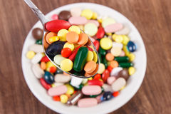 Medical pills on teaspoon and heap of colorful medical capsules in background, health care concept Stock Photography