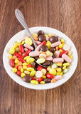 Medical pills on teaspoon and heap of colorful medical capsules on plate, health care concept Stock Image