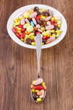 Medical pills on teaspoon and heap of colorful medical capsules on plate, health care concept Stock Photography