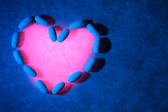 Medical pills on textured background with blue lighting. Pills are arranged in the form of a heart and are lit with red light. Royalty Free Stock Images