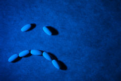 Medical pills on textured background with blue lighting. Pills are arranged in the form of a sad face.  Stock Images