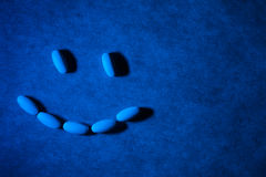 Medical pills on textured background with blue lighting. Pills are arranged in the form of a smiling face. Royalty Free Stock Photography