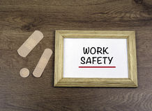 """Medical plasters and wooden frame with text: """"Work Safety"""" o Royalty Free Stock Photography"""