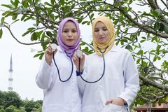 Medical practitioner posed with their stethoscope at park. Muslimah medical practitioner posed with their stethoscope at park during lunch hour Royalty Free Stock Image