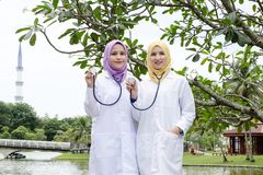 Medical practitioner posed with their stethoscope at park. Muslimah medical practitioner posed with their stethoscope at park during lunch hour Stock Photography