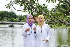 Medical practitioner posed with their stethoscope at park. Muslimah medical practitioner posed with their stethoscope at park during lunch hour Stock Photo