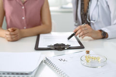 Medical prescription form, capsules and pills are lying against the background of a doctor and patient discussing health Stock Photography