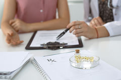 Medical prescription form, capsules and pills are lying against the background of a doctor and patient discussing health Royalty Free Stock Images