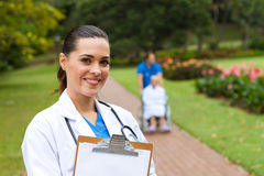 Medical professional. Young female medical professional in park, background is her colleague push senior patient on wheelchair Royalty Free Stock Photo