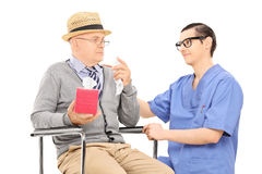Medical professional comforting a sad senior man Stock Photography