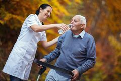Medical professional helping a senior man with walker drink a wather. Medical professional helping a senior men with walker drink a wather in park Royalty Free Stock Images