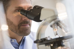 Medical Professional Looking Through Microscope Royalty Free Stock Photo