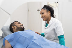 Medical Professional Preparing Man For X-ray Scan In Hospital. Young female medical professional preparing men for X-ray scan in examination room Stock Photos