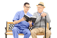 Medical professional reading to an elderly Stock Photo