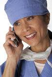 Medical Professional in Scrubs on the Phone. Closeup, cropped view of an Asian female medical professional wearing scrubs and talking on a cell phone. Vertical Stock Images