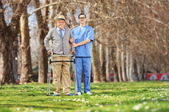 Medical professional and a senior posing in park. On a beautiful sunny day Royalty Free Stock Photography