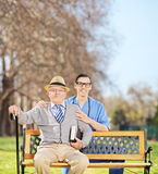 Medical professional and a senior posing in park Royalty Free Stock Photo