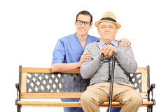 Medical professional and senior sitting on bench Royalty Free Stock Photography