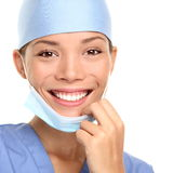 Medical professional: young doctor. Or woman nurse smiling taking her surgeon mask off. Closeup portrait isolated on white background Royalty Free Stock Photography