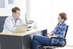 Medical professionals Caucasian man reassuring and talking with young woman stress patient. stock images